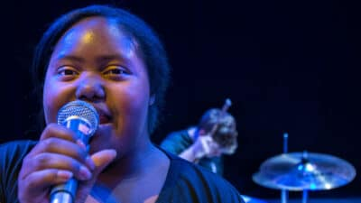 A singer sings into a microphone while a drummer plays behind her