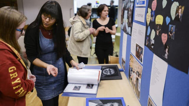 A person with long black hair wearing a denim pinafore shows another person with long hair a portfolio in front of a display at the Academy Open Day