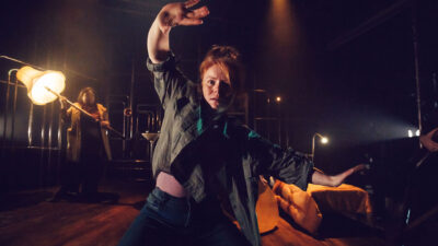 A performer with red hair tied into a bun wearing jeans and a shirt holding their hands up with a shocked expression on their face. A performer in the background is holding a large lamp.