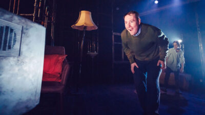 A performer with short hair, a green jumper and dark trousers has a happy, surprised look on their face