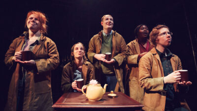A group of five performers around a table with a yellow teapot on it, all wearing matching brown jackets all holding matching dark brown mugs