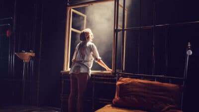 A performer stood beside a bed leaning out of a window frame into bright light and smoke