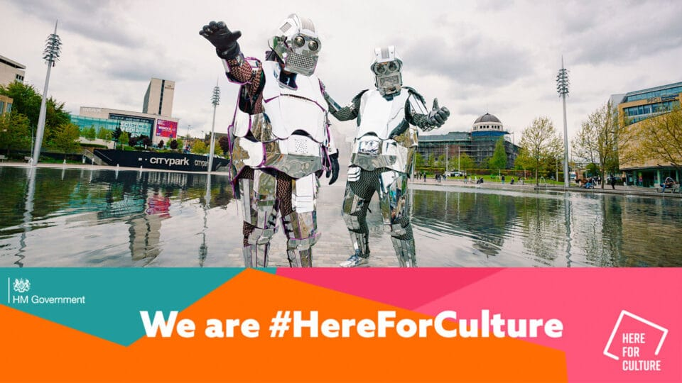 Performers wearing robot costumes pose in Bradford city centre