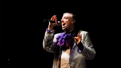 A performer wearing a silver sequin jacket with fancy purple neck ruffle, singing into a microphone