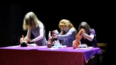 Three performers changing the nappies of three toy baby dolls
