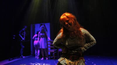 Performer with long red hair wearing a stripy t-shirt and belt with gold beads, stands with their hands on their hips