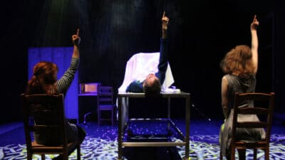 Three performers on stage all pointing to the sky, two in chairs and the one in the middle lying on a table covered from the chest down by a white sheet
