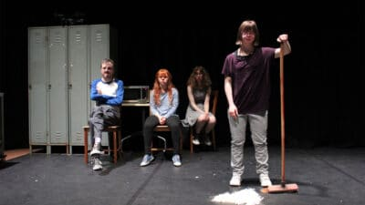 Four performers on stage, three sat in chairs next to a set of lockers and a microwave, one stood holding a broom