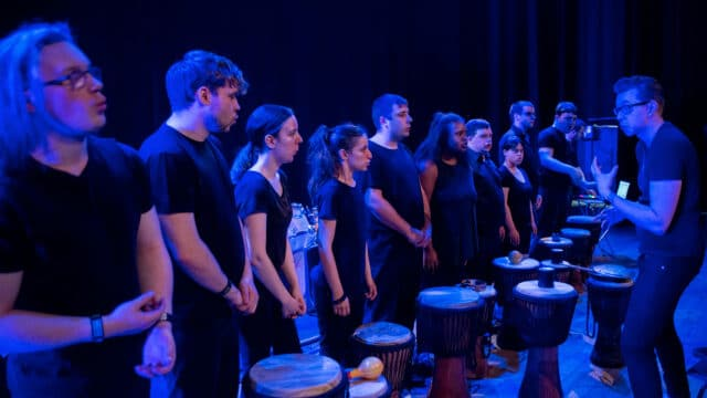 A group of performers all wearing black stood in a line in front of some bongo drums