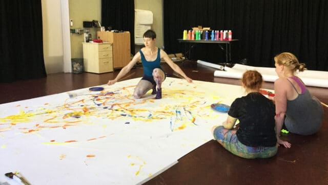 An artist knelt upon a very large canvas scattering yellow and blue paint around
