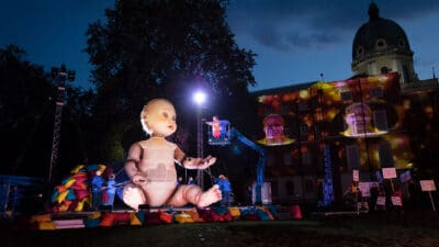 Performer raised in a cherry picker at eye-level with giant model baby that has puppetry arms being moved by a team of puppeteers. In the background are performers holding protest signs and a person's face is projected in lights twice onto a building behind them.