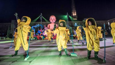 A group of performers wearing hazmat suits, carrying brooms, dancing in front of a giant model of a baby