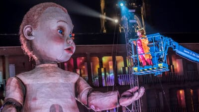 A performer stood in a cherry picker raised up to the eye level of the giant model baby