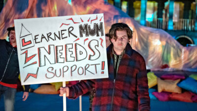 A performer wearing a check fleece holds a sign that reads 'Learner Mum needs support!'
