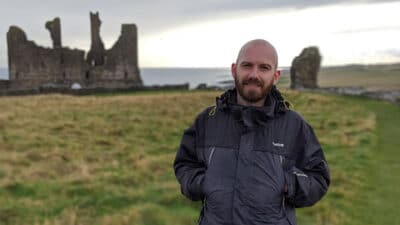 Rob Abbey wearing a rain jacket stood in a field by some ruins