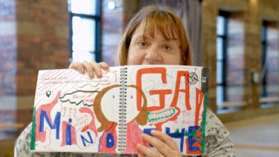 A person holding up an open notebook full of colourful drawings and words