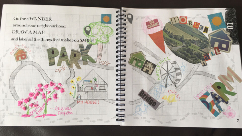 An open notebook with text that reads 'Go for a wander around your neighbourhood. Draw a map and label all the things that make you smile.' with a hand-drawn map, drawings, and a collage of photos and letters stuck onto the pages