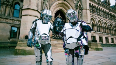 Two people wearing suits made of sheets of silver, resembling robots