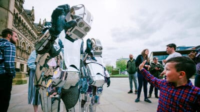 Two people wearing suits made of sheets of silver, resembling robots surrounded by people, one waving at a small child wearing a check shirt who waves back