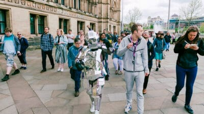A person wearing a suit made of sheets of silver, resembling a robot, walking with a group of people