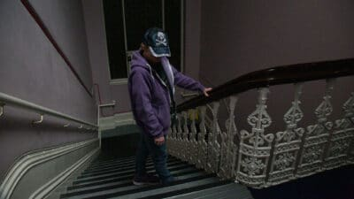 A person stood on some stairs, wearing jeans, a purple zip-up hoodie and baseball cap with a silver skull and crossbones on it