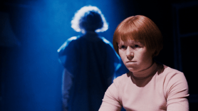A woman with red hair looks upset in the foreground fo the image. In the background is a ghostly figure with her back to the camera lit in blue light.