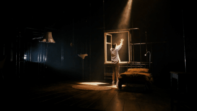 A woman in a white shirt and brown trousers has her back to the camera. she is opening a window. A shaft of light is shining through the window.
