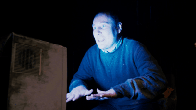 A possessed looking man stares intently at a television set with his hands out in front of him. The TV set is lighting up his face.