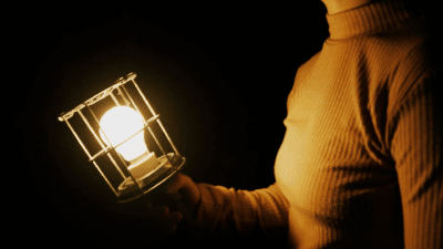 The torso of a woman is visible on the right of the image. She is holding a bright lightbulb encased in a wire frame/
