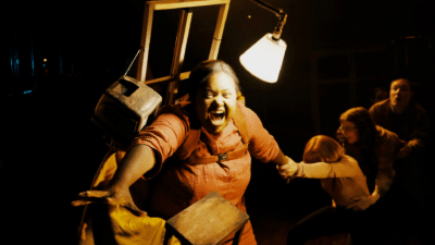 A woman looks terrified surrounded by small household items including a window, a light and a television. A woman int he background is reaching out to her.