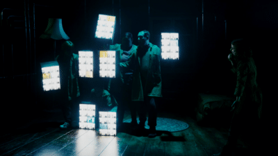 Four people hold seven light boxes to make the shape of a person. A woman to the right of the image appears to be conducting them.