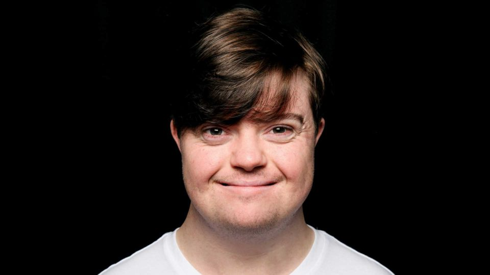 An image of Liam Bairstow - an early thirties white man with downs syndrome. He has dark hair swept across his forehead and is wearing a white t-shirt